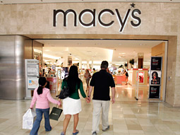 Macy's on Wednesday cut its full-year earnings outlook as profits slipped, but said it will continue to make investments in marketing.
